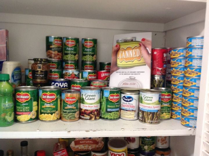 Canned vegetables and fish on a pantry shelf