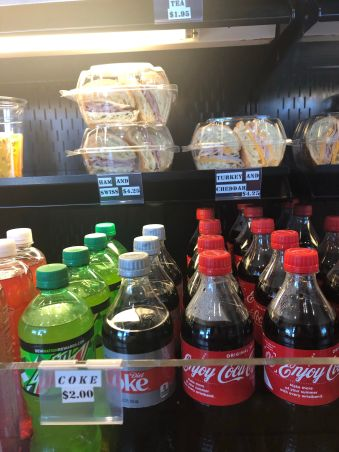 ham and cheese sandwiches and soda on a shelf in a refrigerated cabinet