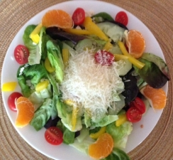 plate of fresh vegetables topped with shredded cheese