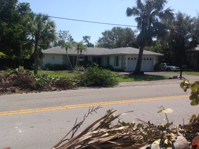 palm tree in front of a house and piles of vegetative debris