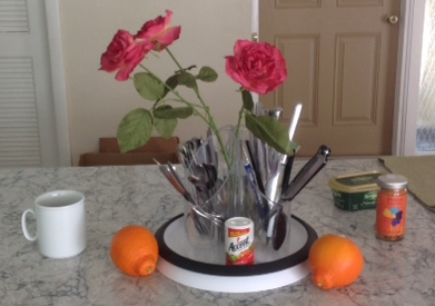 kitchen island scene with artificial roses cutlery, oranges and a coffee cup