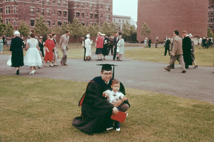author of this post in cap and gown holding a young son in his arms