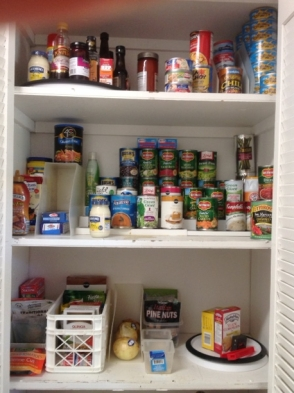 three shelves primarily of canned foods