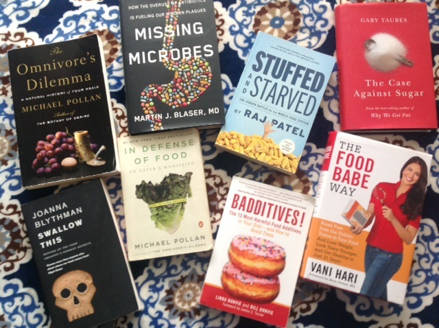 a display of books including Omnivore's Dilemma, Missing Microbes, Stuffed and Starved, The Case Against Sugar, Swallow This, In Defense of Food, Baddititves, and The Food Babe Way