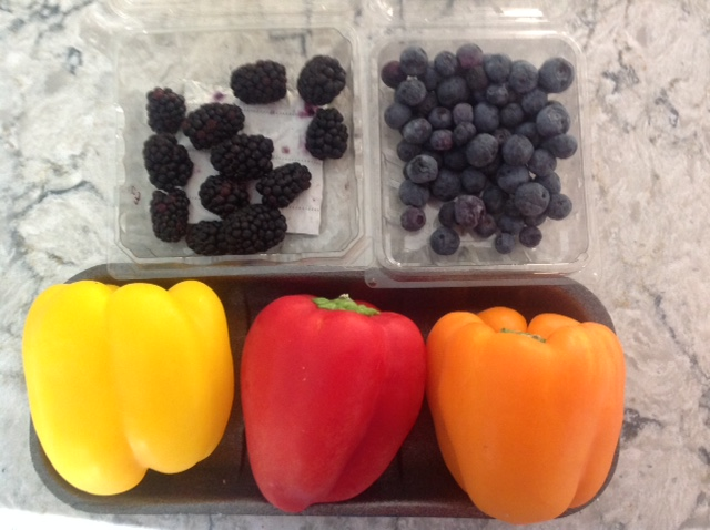some remaining blackberries, blueberries with a yellow, red, and orange bell peppers
