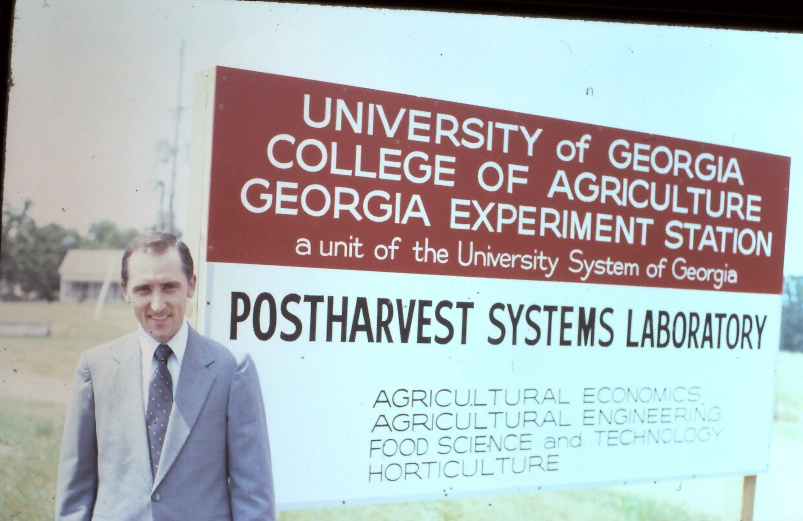 photo of the author next to a sign identifying Agriculutral Economics, Agricultural Engineering, Food Science and Technology and Horticulture as major players