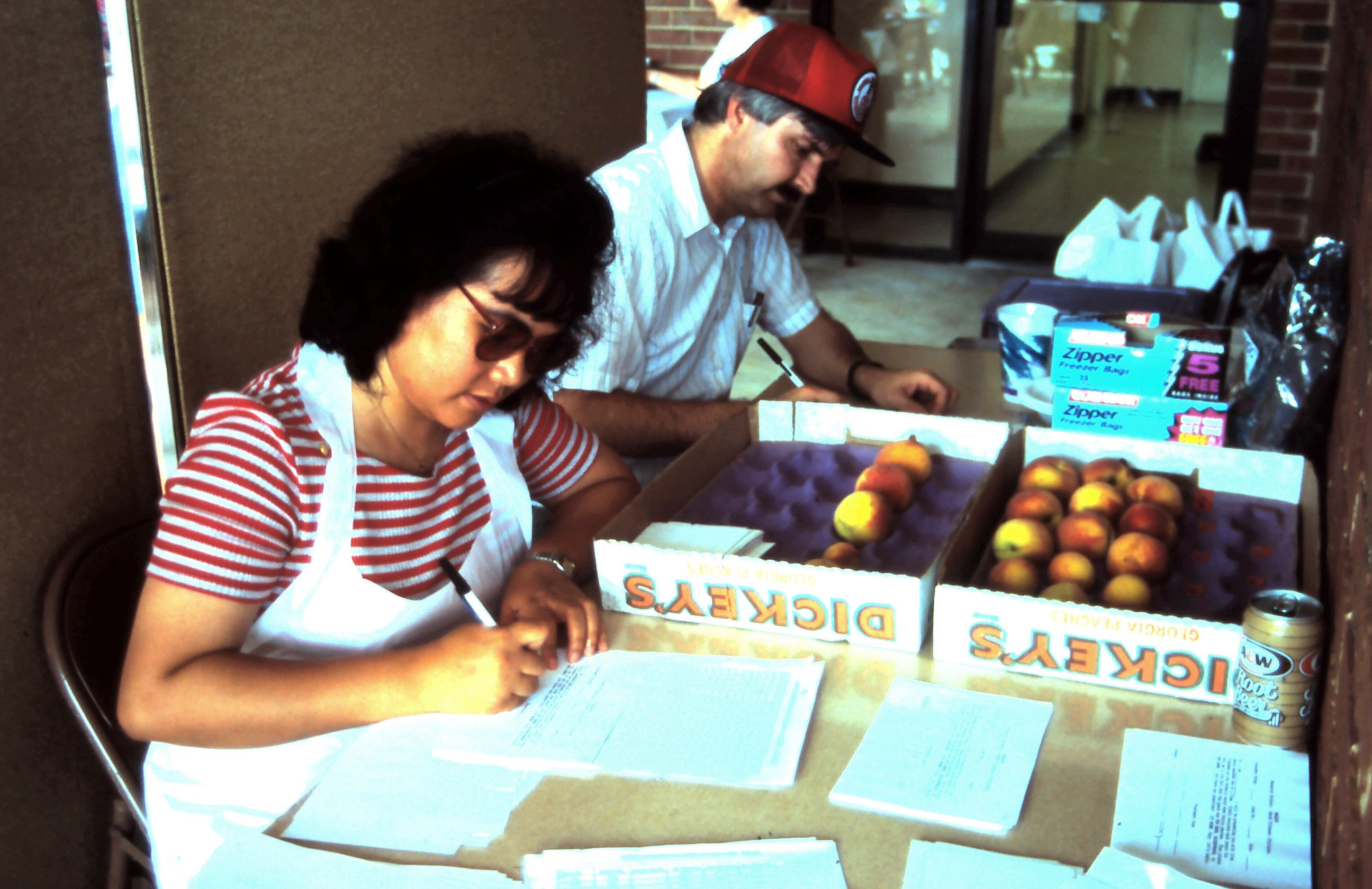 two people preparing score sheets for peach tests