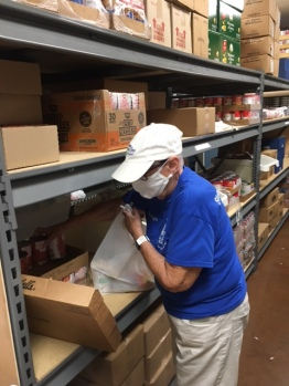 masked woman bagging processed foods