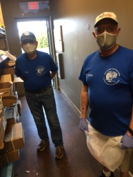 two men with masks in the first aisle of the pantry