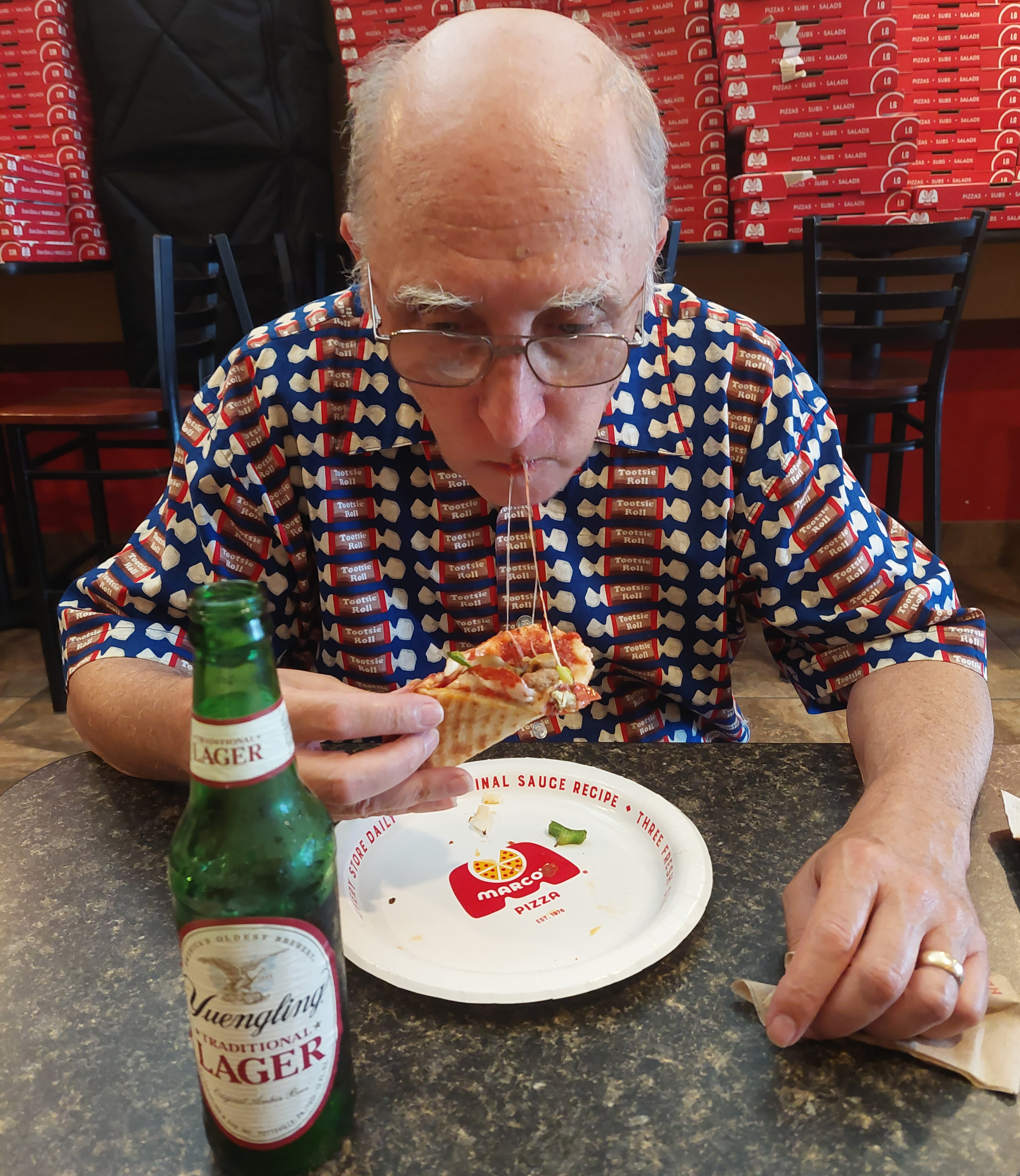 author eating a thin-crust pizza New York style