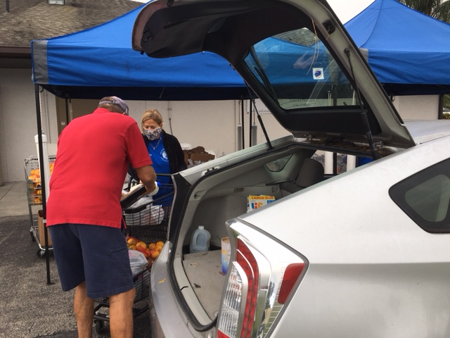 Food pantry volunteer loading up trunk of car with whole and packaged foods.