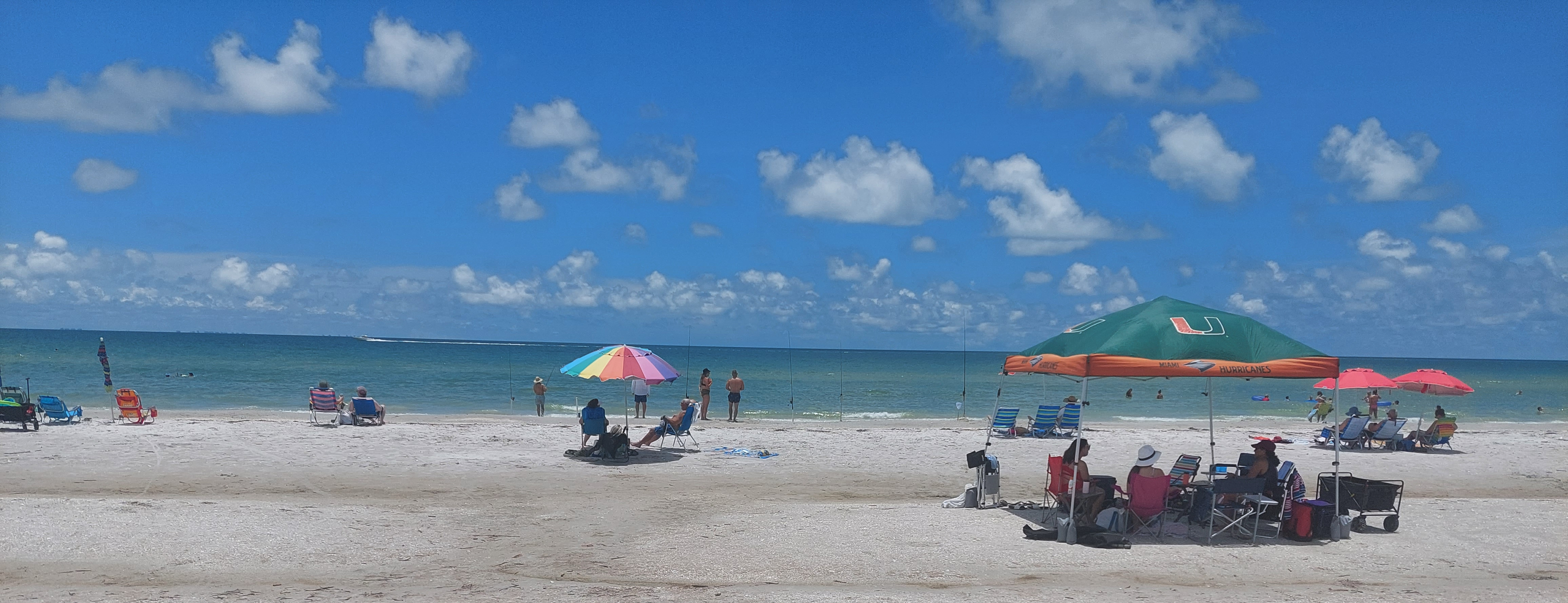 people enjoying a beautiful day at the beach with blue cloudy skies and blue waterwith