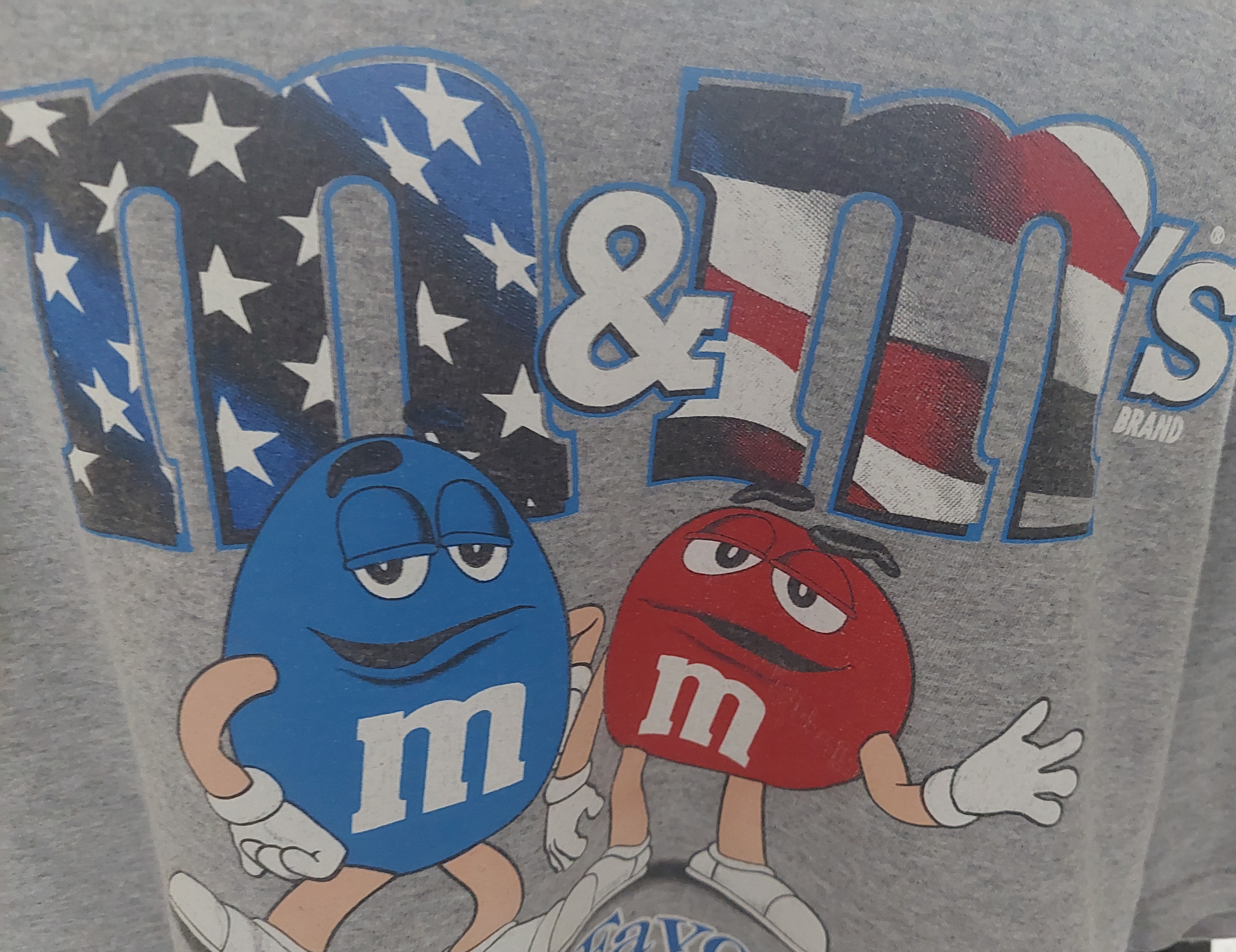 blue and red M&Ms wave to the audience with stars and stripes in the background